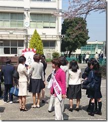 入学式の行われる校門前であいさつする私・白井まさ子